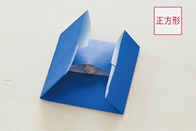 正方形の作り方 キャンディを折り紙の中央に置き、上下、両端を折って正方形を作る。中身が出ない程度に、マスキングテープでとめる。