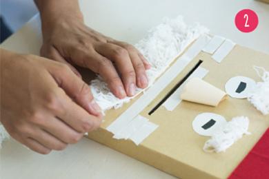 顔のパーツをのりで貼りつける。ヒゲは口の周りに両面テープを貼り、毛足の長い毛糸をつける。毛糸がなければ白いタオルなどでもOK!