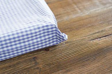 2.裏地の布の表面どうしを重ねて2つ折りにして両側を縫い、袋状にする。このとき、仕上げ時に裏返すための返し口を片側のみ10cm程度縫わずにおく。そして、底部分の角をそれぞれ三角に開いて折って縫い、マチを作る。