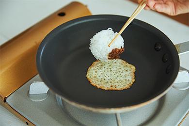 チーズのふちの部分に焼き色がつき、フライパンと接している面が少し固まってきたところでおにぎりを置いて裏返すのがポイント。チーズは火が入りすぎると苦みが出るので、タイミングに気をつけて。
