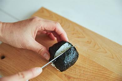 海苔を巻いたおにぎりに具材をはさむための切り込みを入れます。湿らせた布巾で包丁を拭いてから切ると、きれいな切り込みになります。