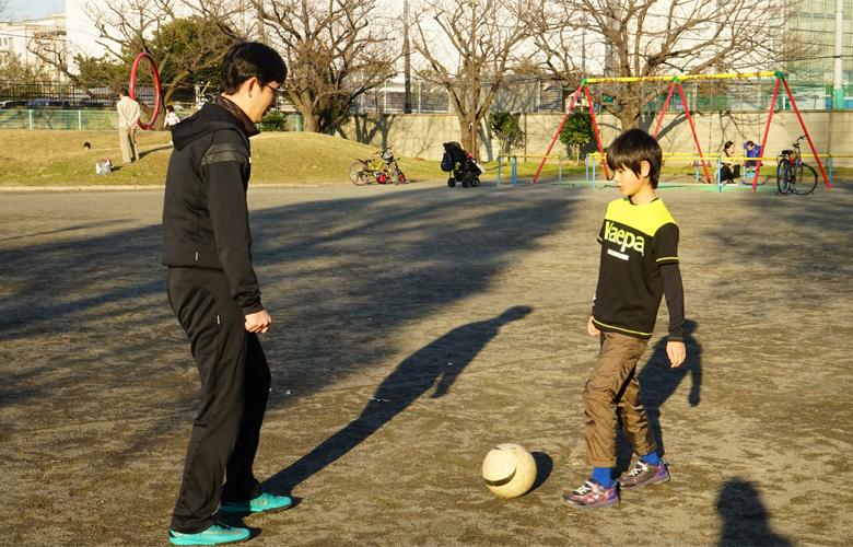 息子とサッカーをするお父さん