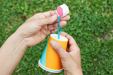 3.ヘアゴムにスーパーボールを固定し、スーパーボールをアルミホイルで包む。紙コップの表面にポスカで顔を描く。